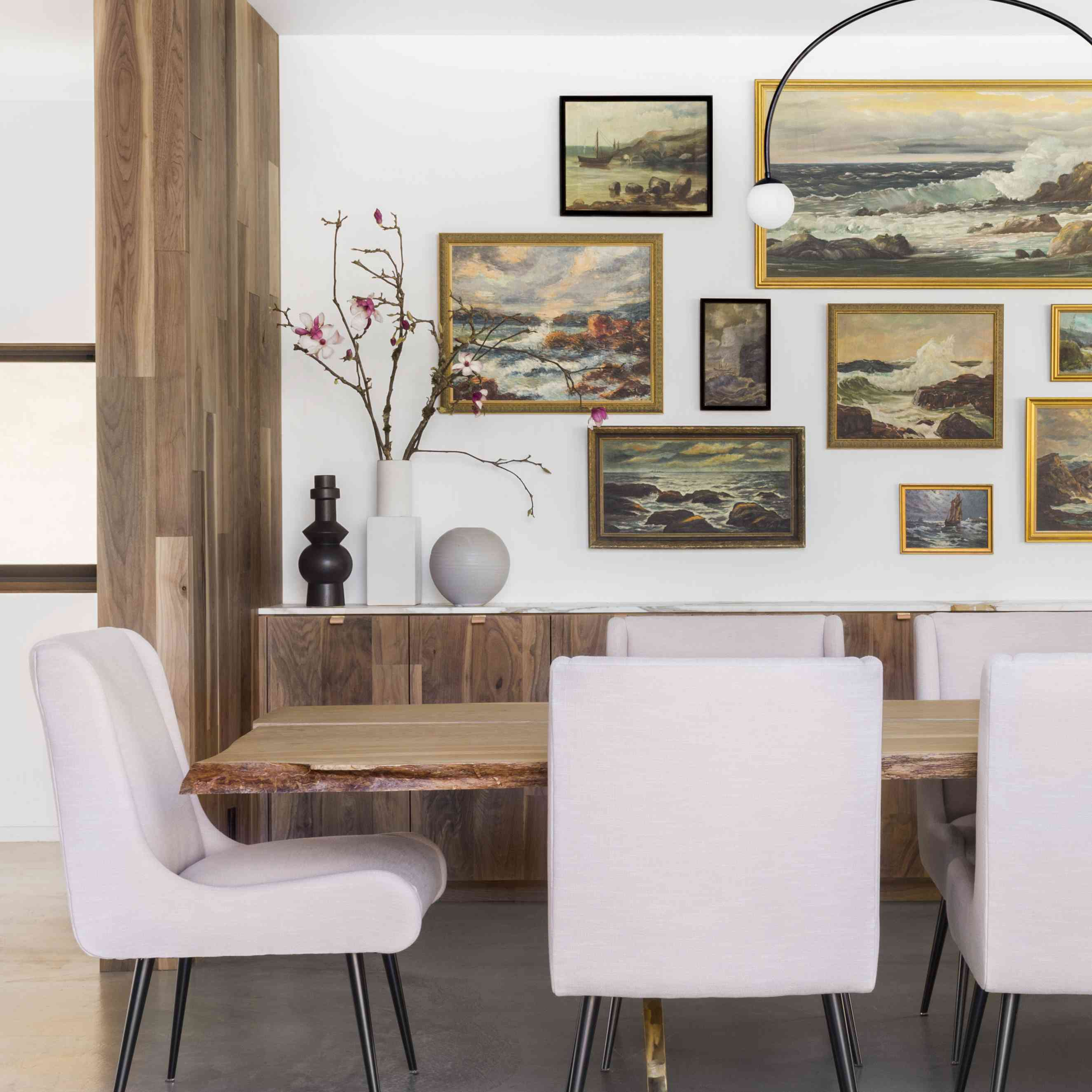 Modern dining room with ornate seascape gallery wall
