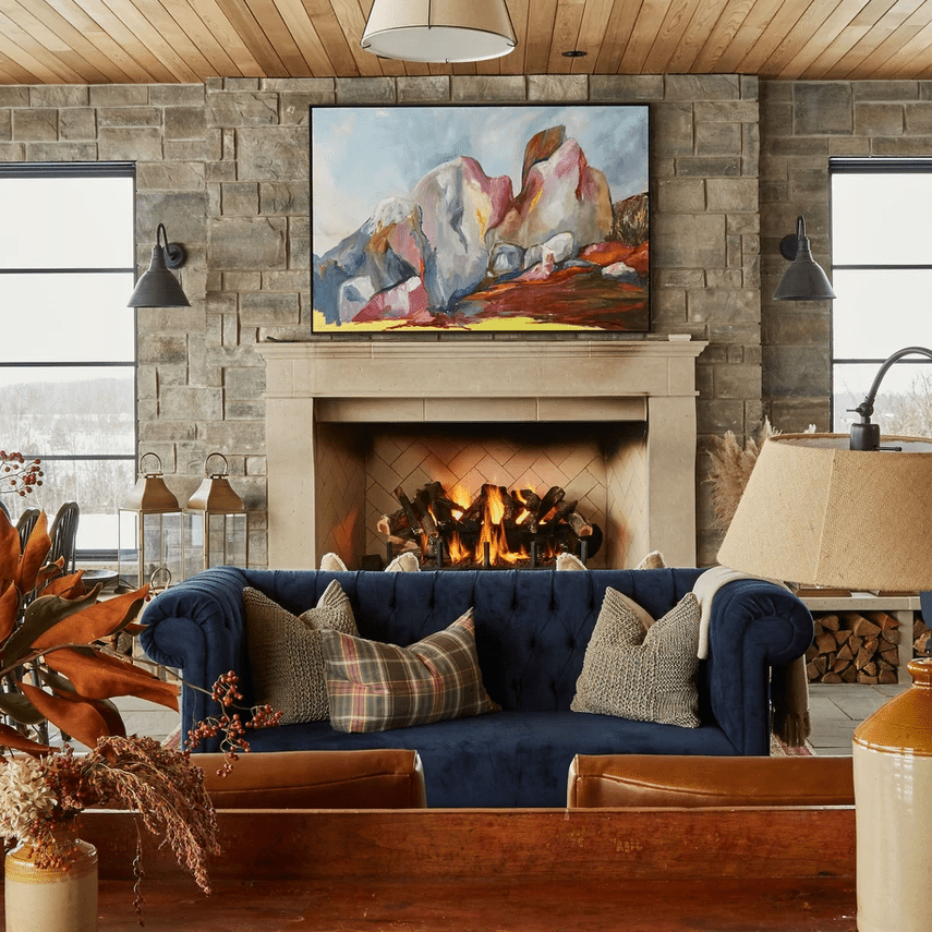 Sitting room with curved sofa and large oil painting.