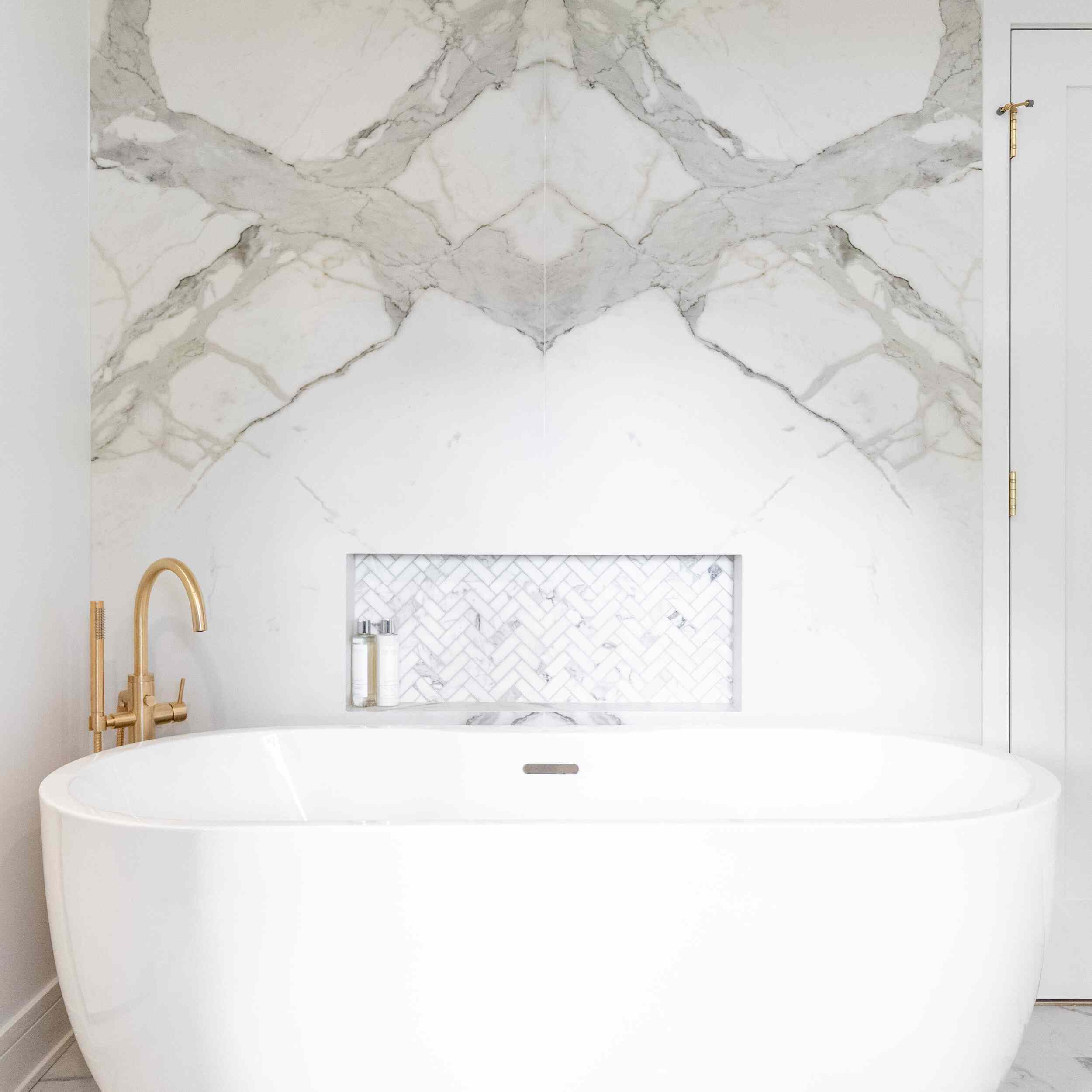 Elegant bathroom with marble, white soaker tub, and metallic accents