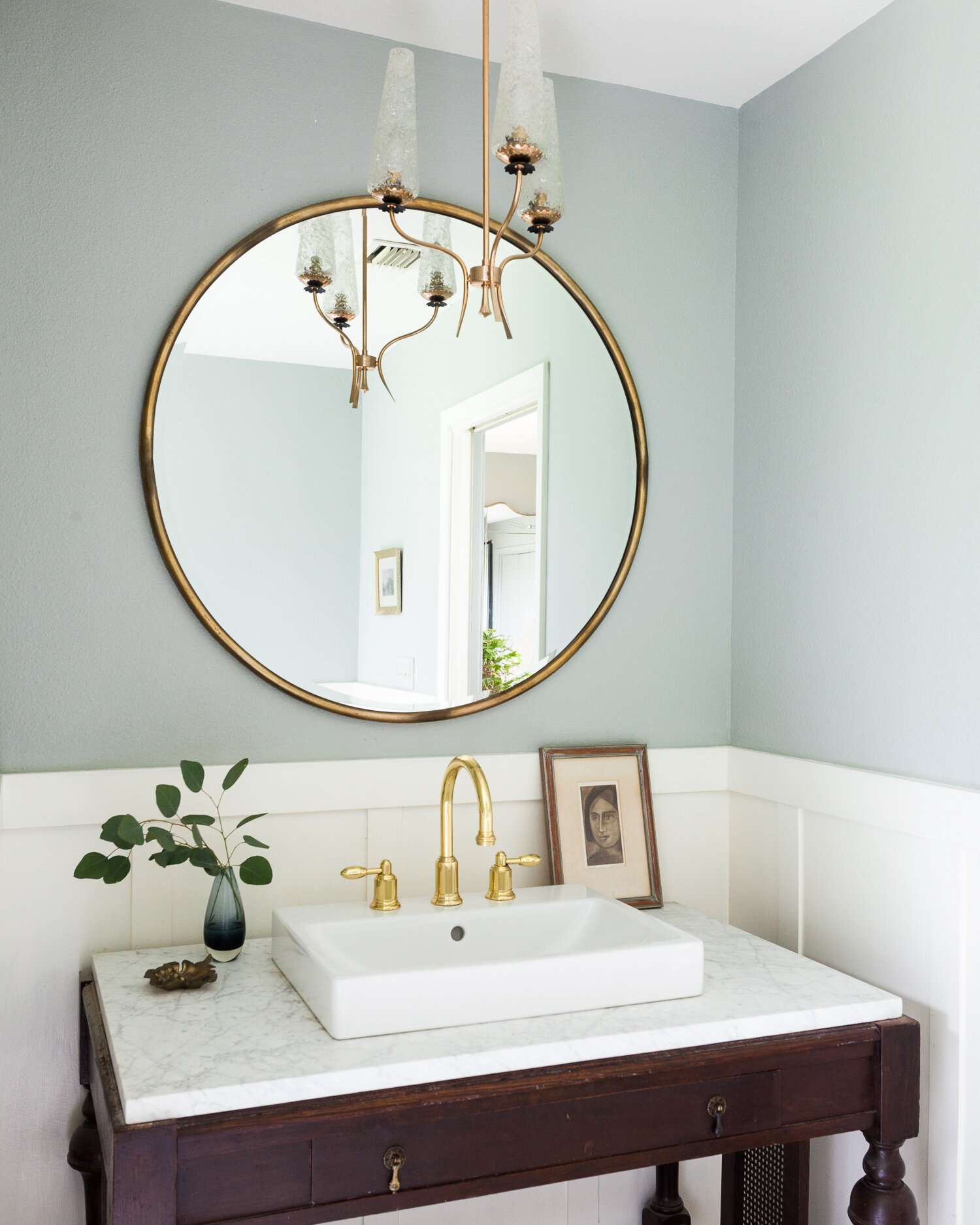A bathroom with an antique vanity and an extra-small sink