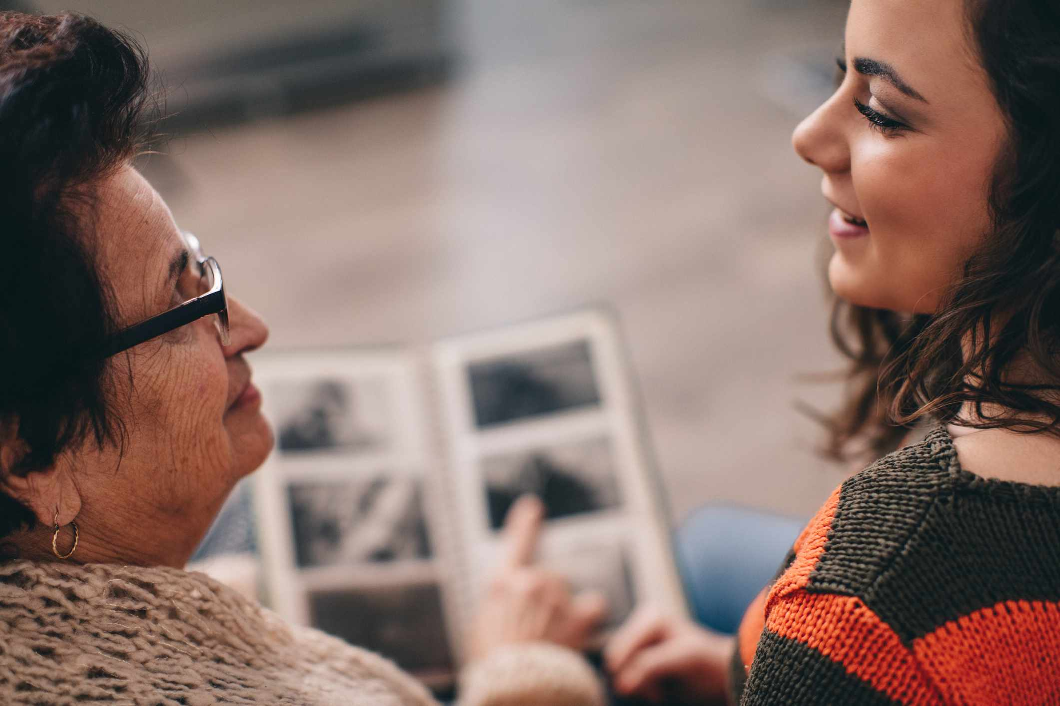 Grandmother and granddaughter look at photo album