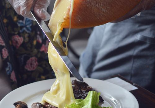 raclette cheese wheel with melted cheese being scraped onto potatoes and mushrooms on plate