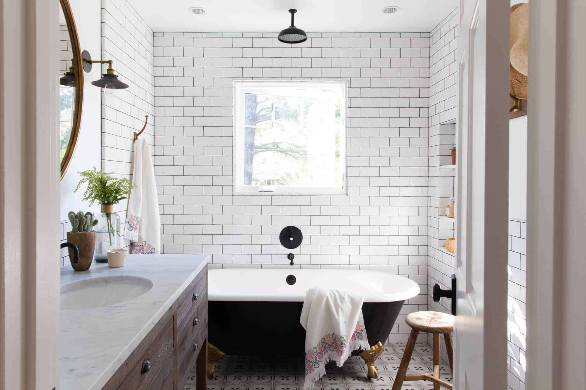 A small primary bathroom with a combination clawfoot tub and open-air shower