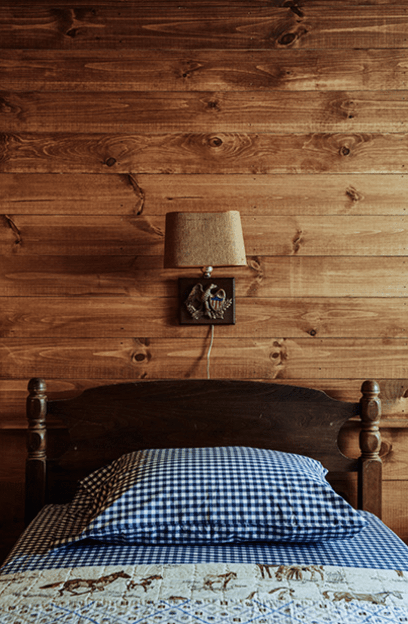 A wood-paneled bedroom with a wooden bed and printed linens