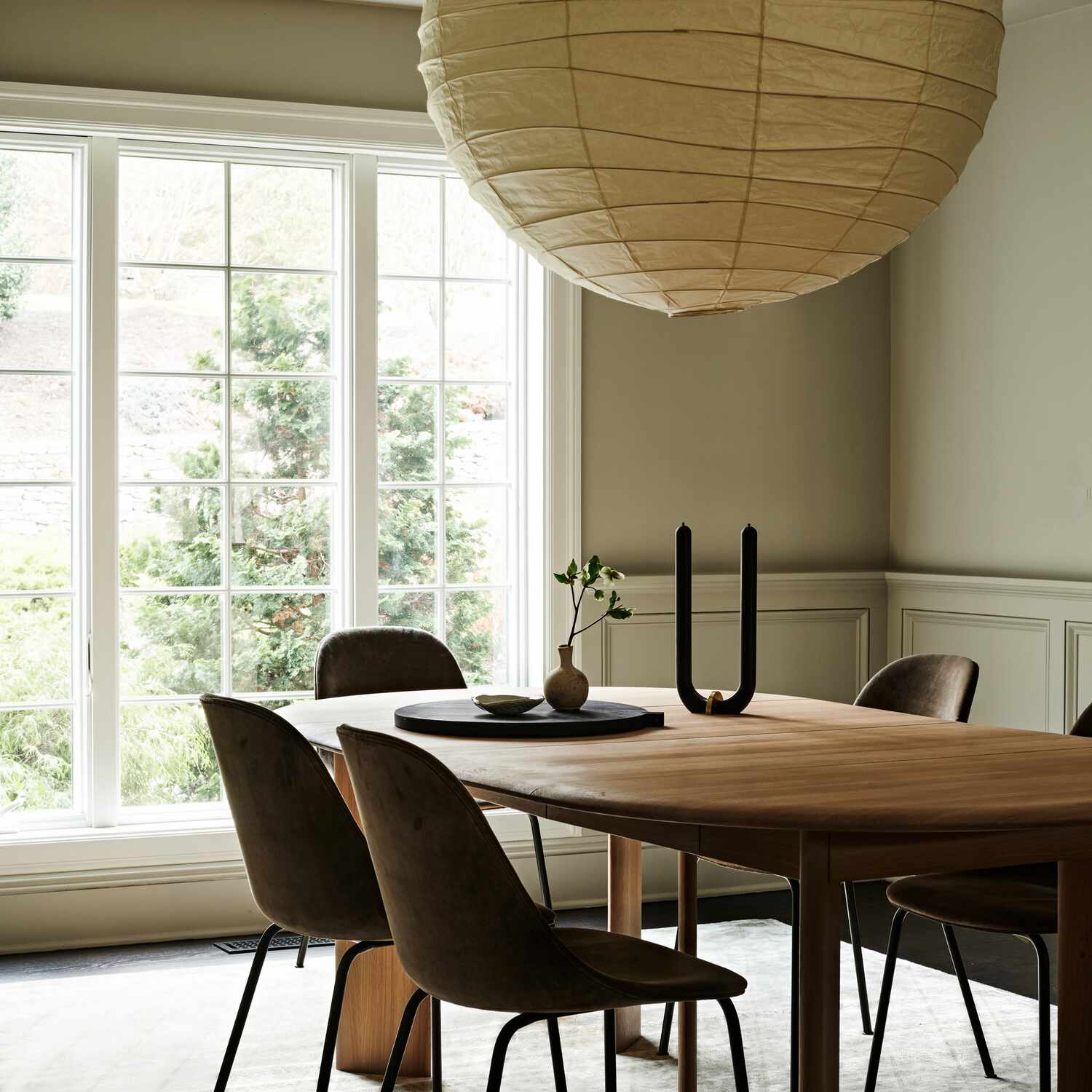 A dining room with a large circular pendant light