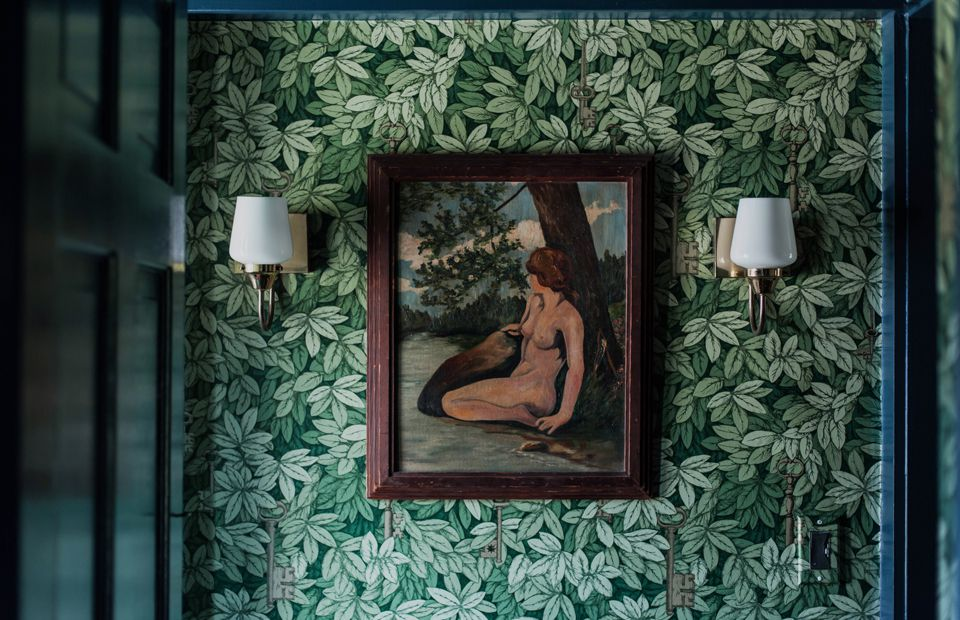A hall covered in green leaf wallpaper with a painting on top