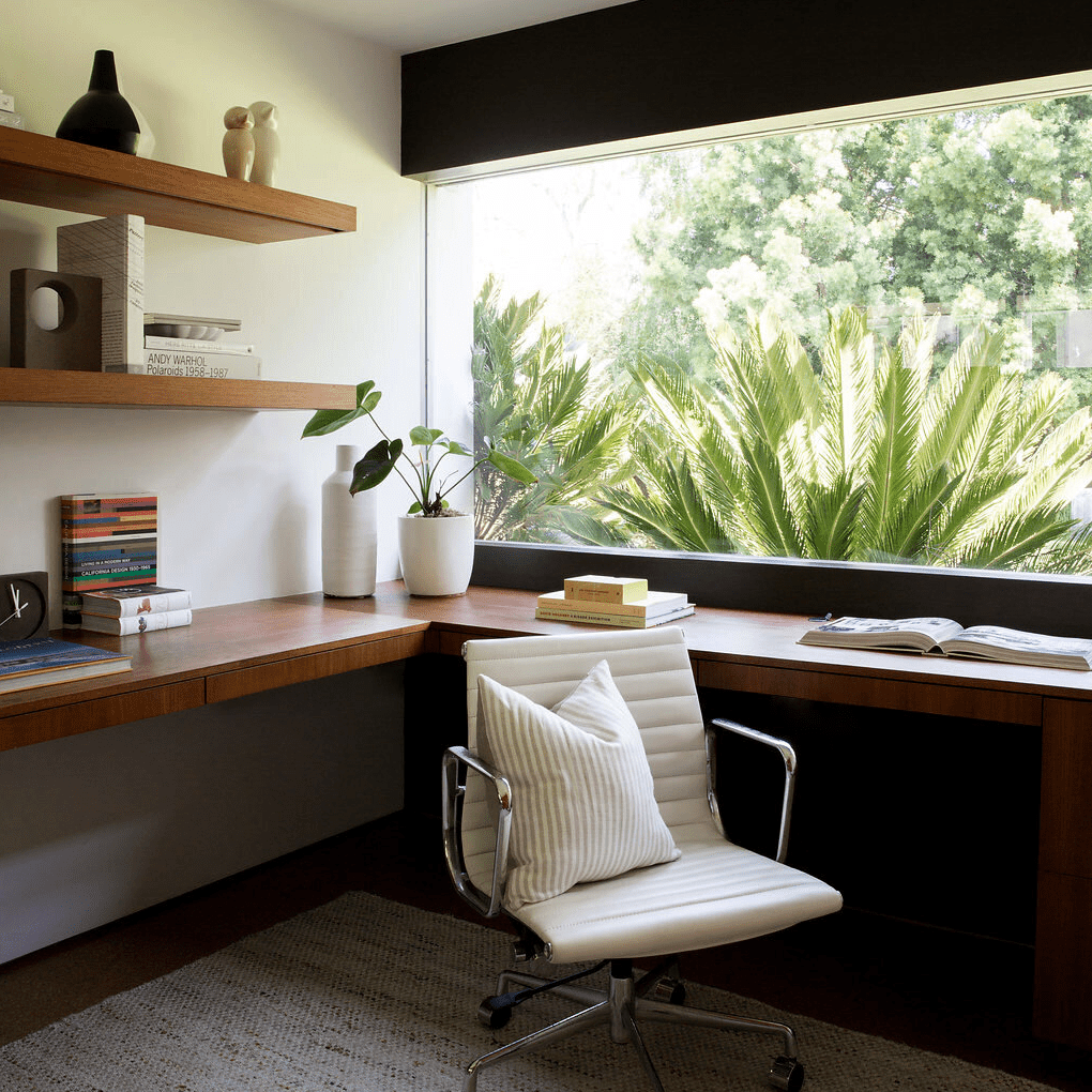 A home office with a wraparound wooden desk and several book-lined shelves