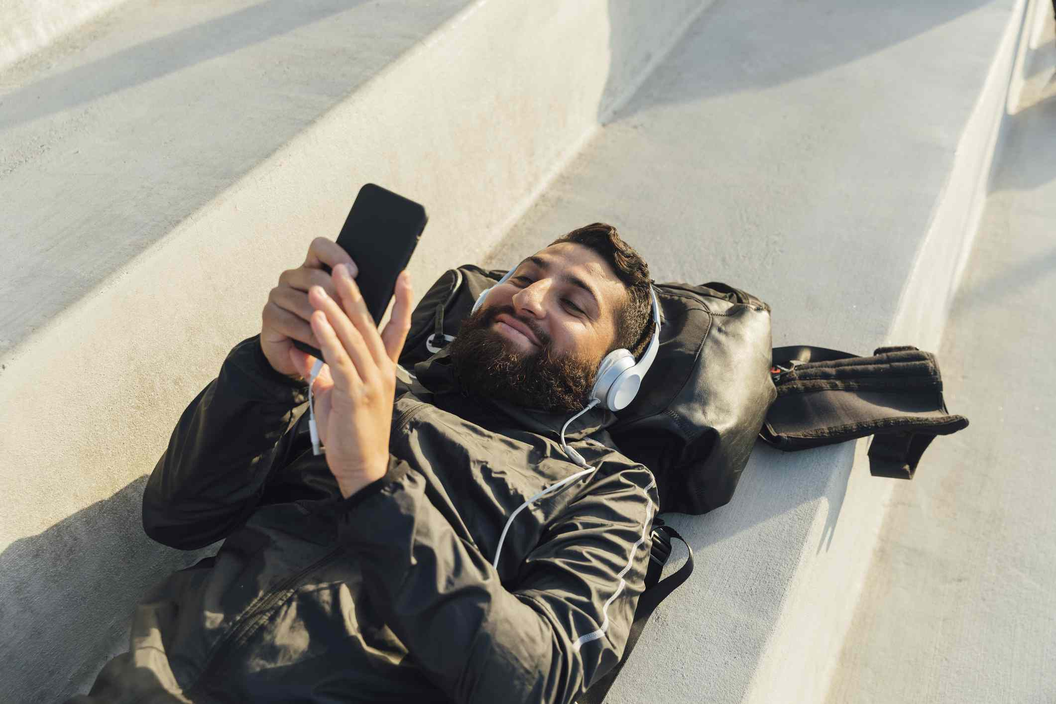 Young man listens to headphones, lying down in stadium