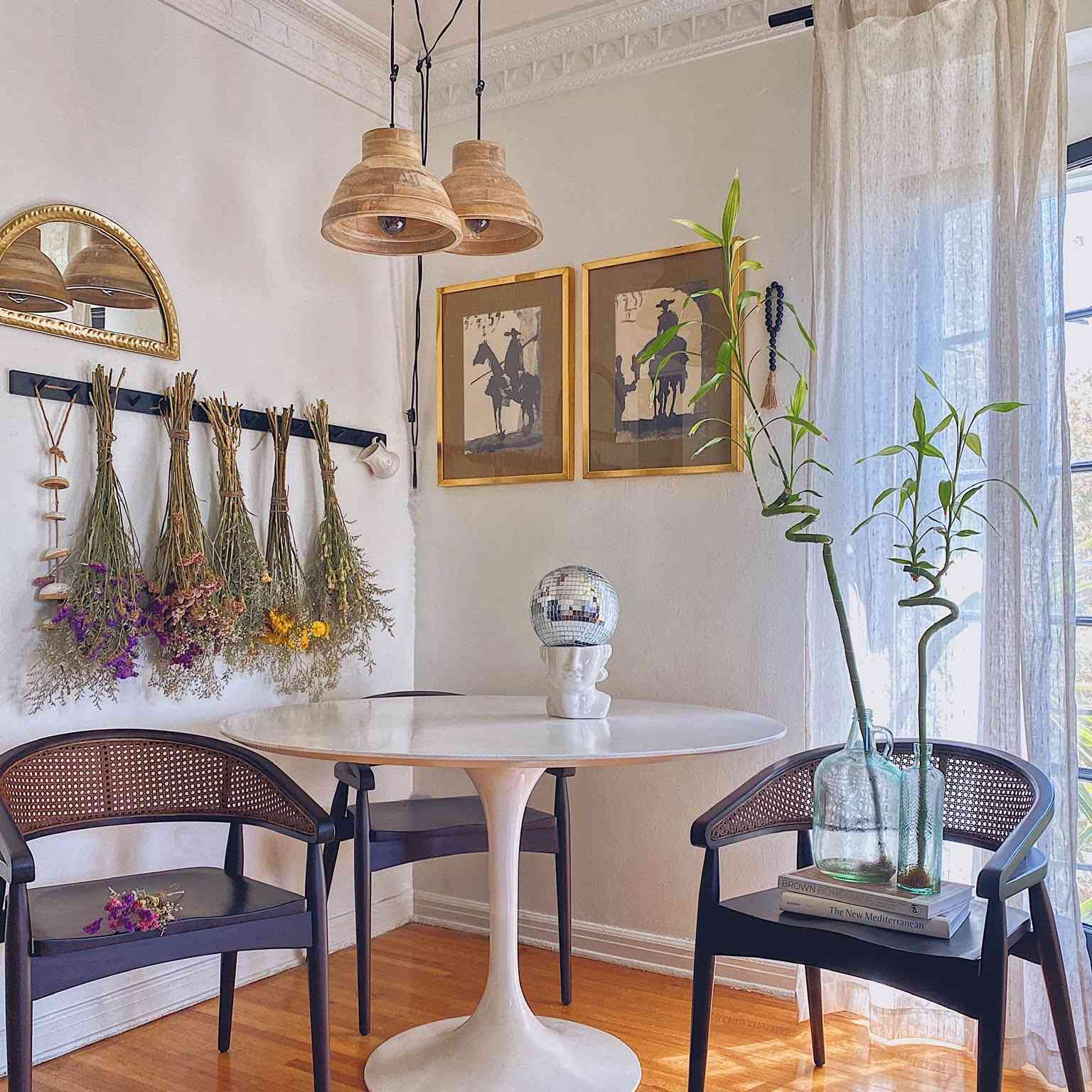 Trendy dining nook with dried florals and rattan pendant lights.