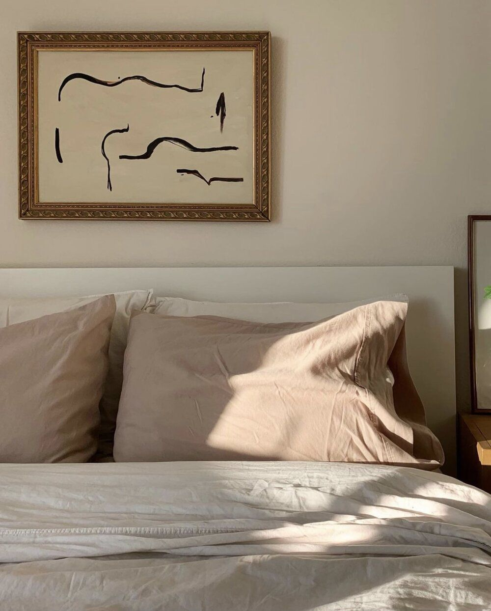 A bed with neutral pillows and soft light.