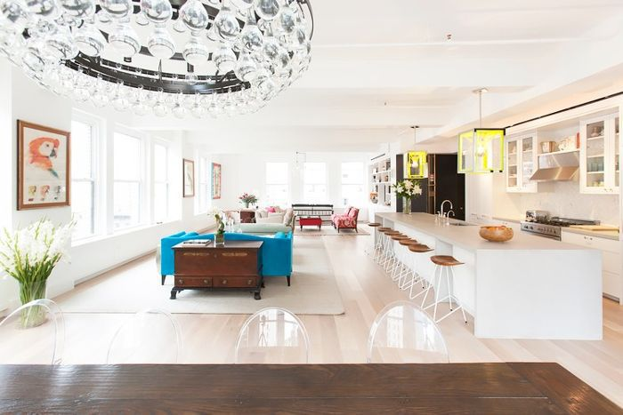 Living room uses repeating rugs to define the space