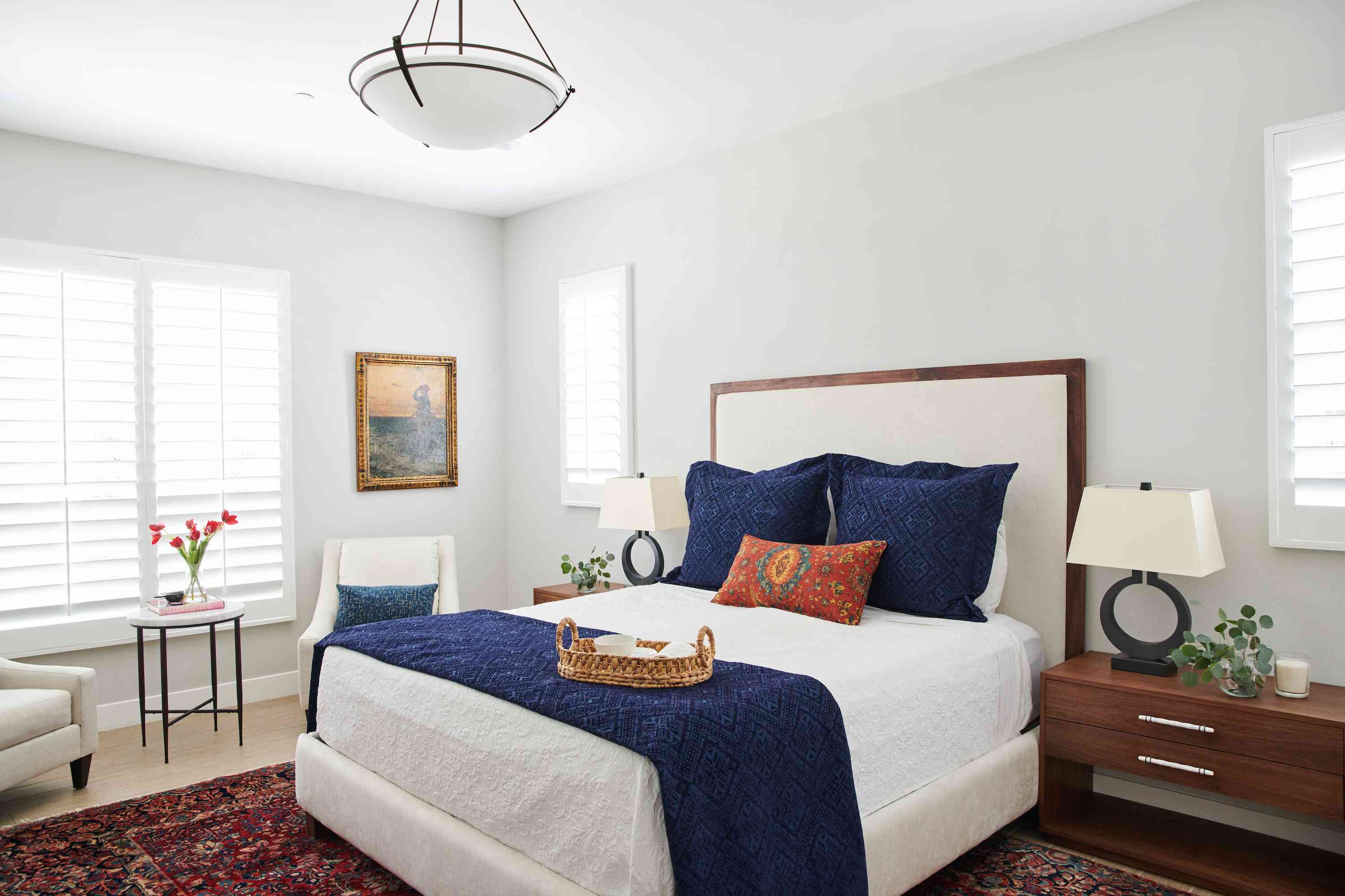 Primary bedroom with navy throw blanket on bed.