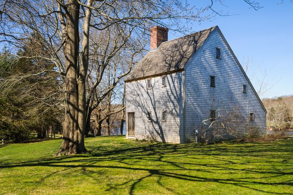 The oldest saltbox house on Cape Cod, with a steeply bitched brown root and brick chimney with vivid green grass and an old oak tree