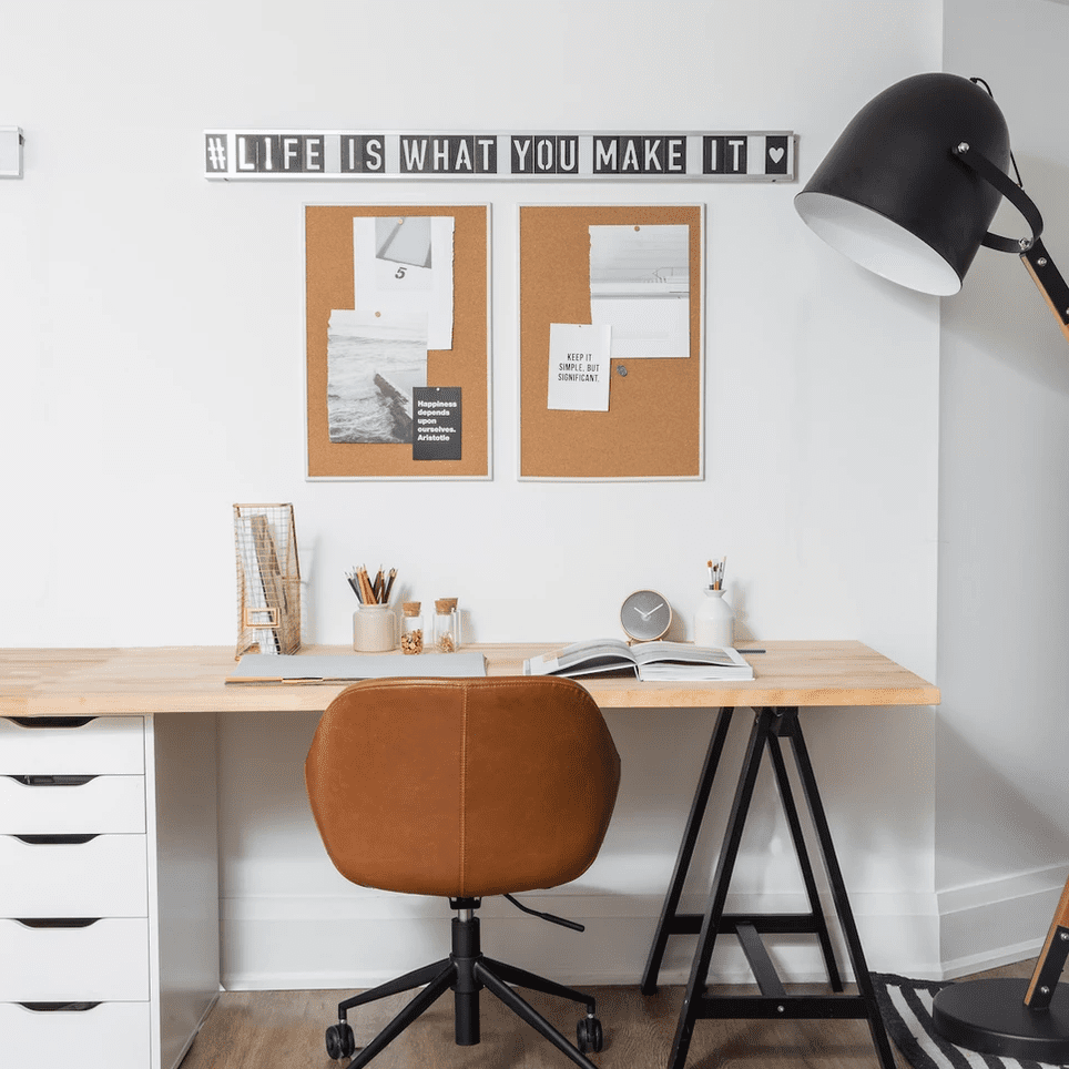 A home office outfitted with several desk accessories, including cork boards, a folder organizer, two pencil cups, and a small clock