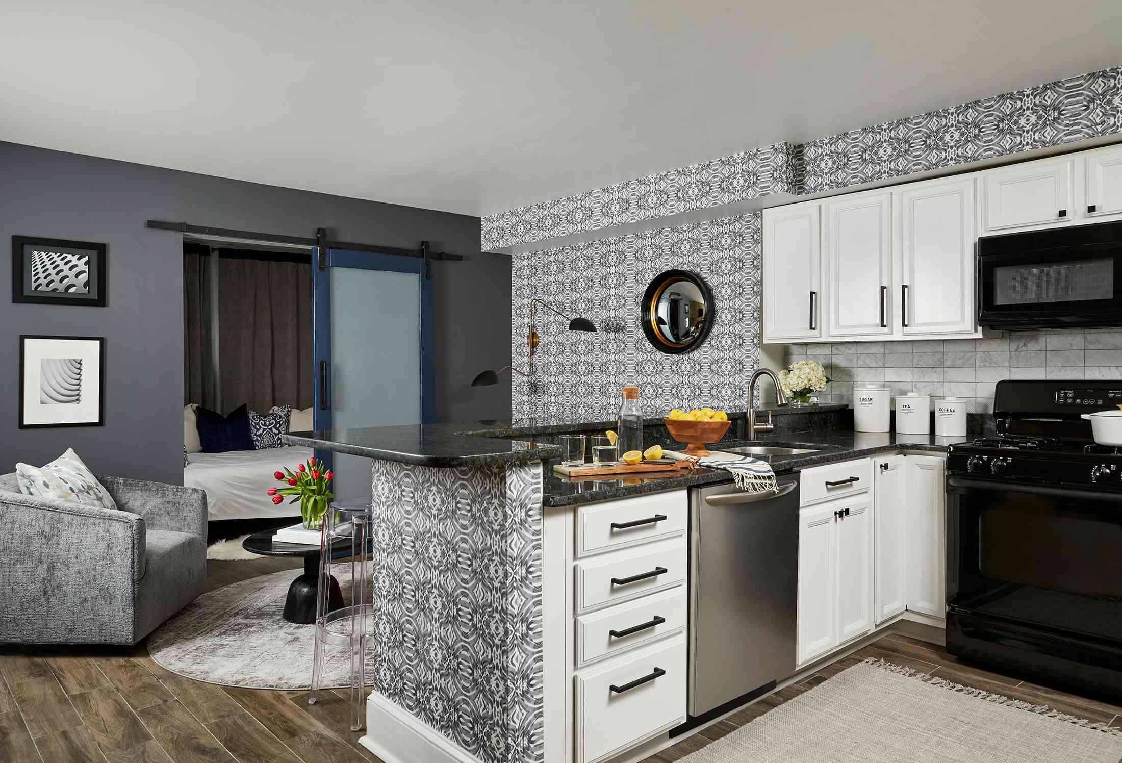 Duke Ellington home tour - kitchen area with white cabinets and black appliances