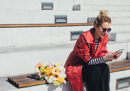 a woman with a bouquet of flowers sitting down texting