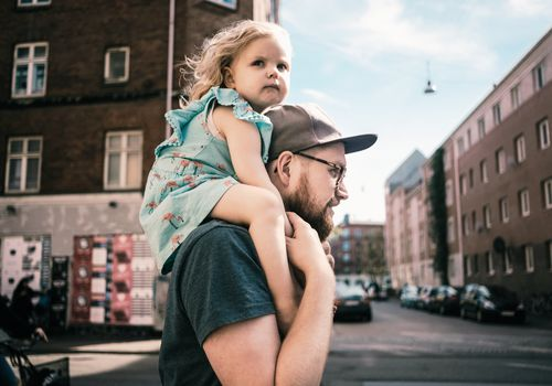 A man walking through the city with his young daughter on piggy back.