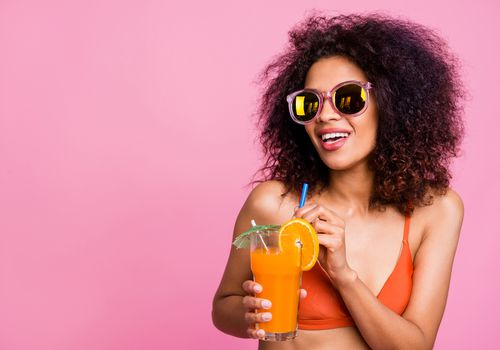 Woman holding a cocktail with orange wheel and tiki umbrella.