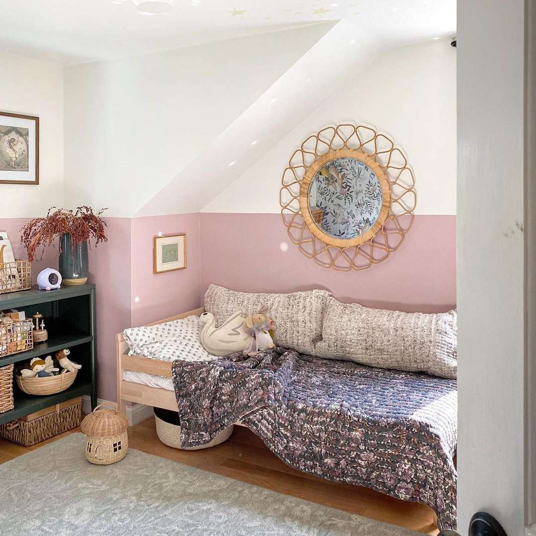 Pink and white bedroom with large rattan mirror.