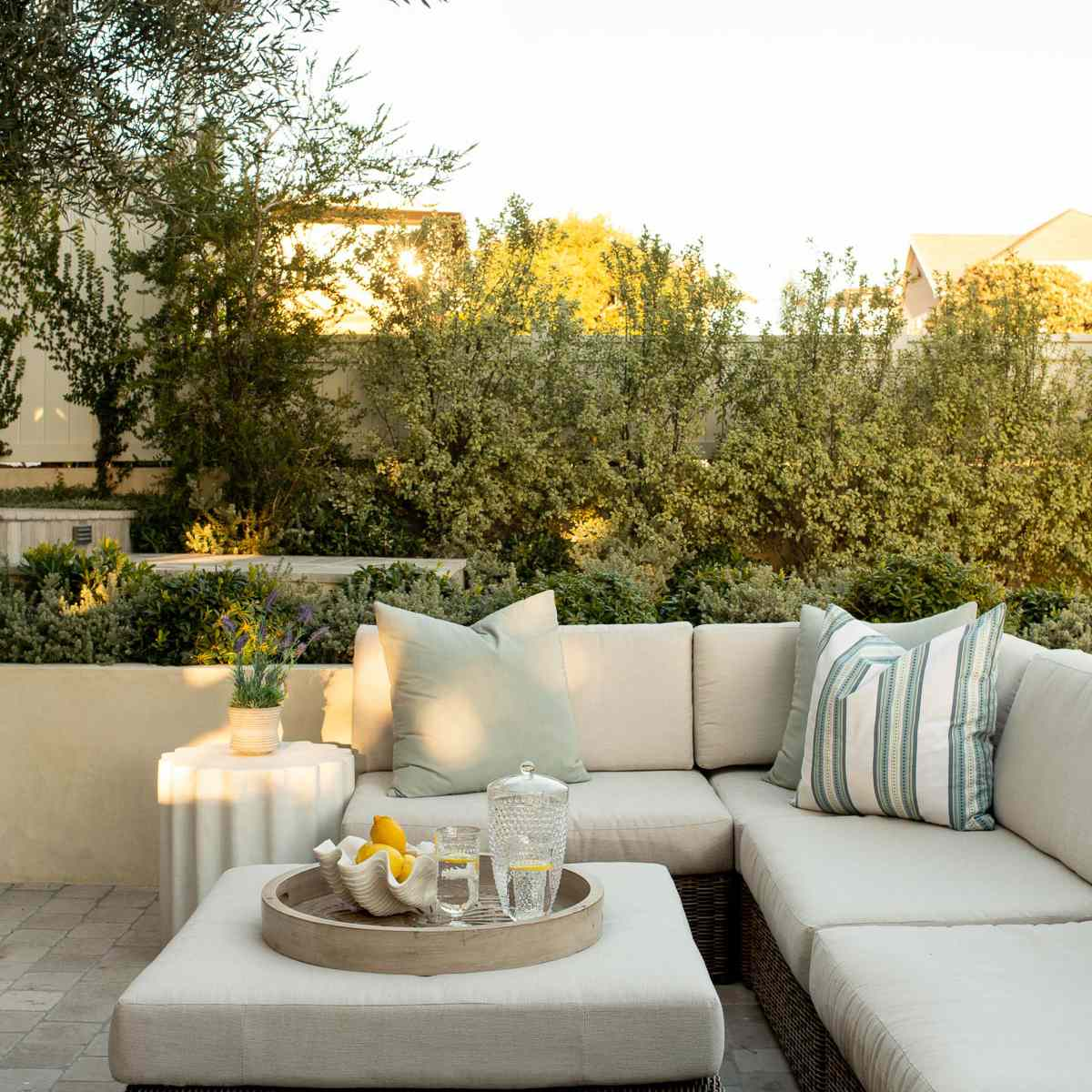 A deck decorated with a large white outdoor couch