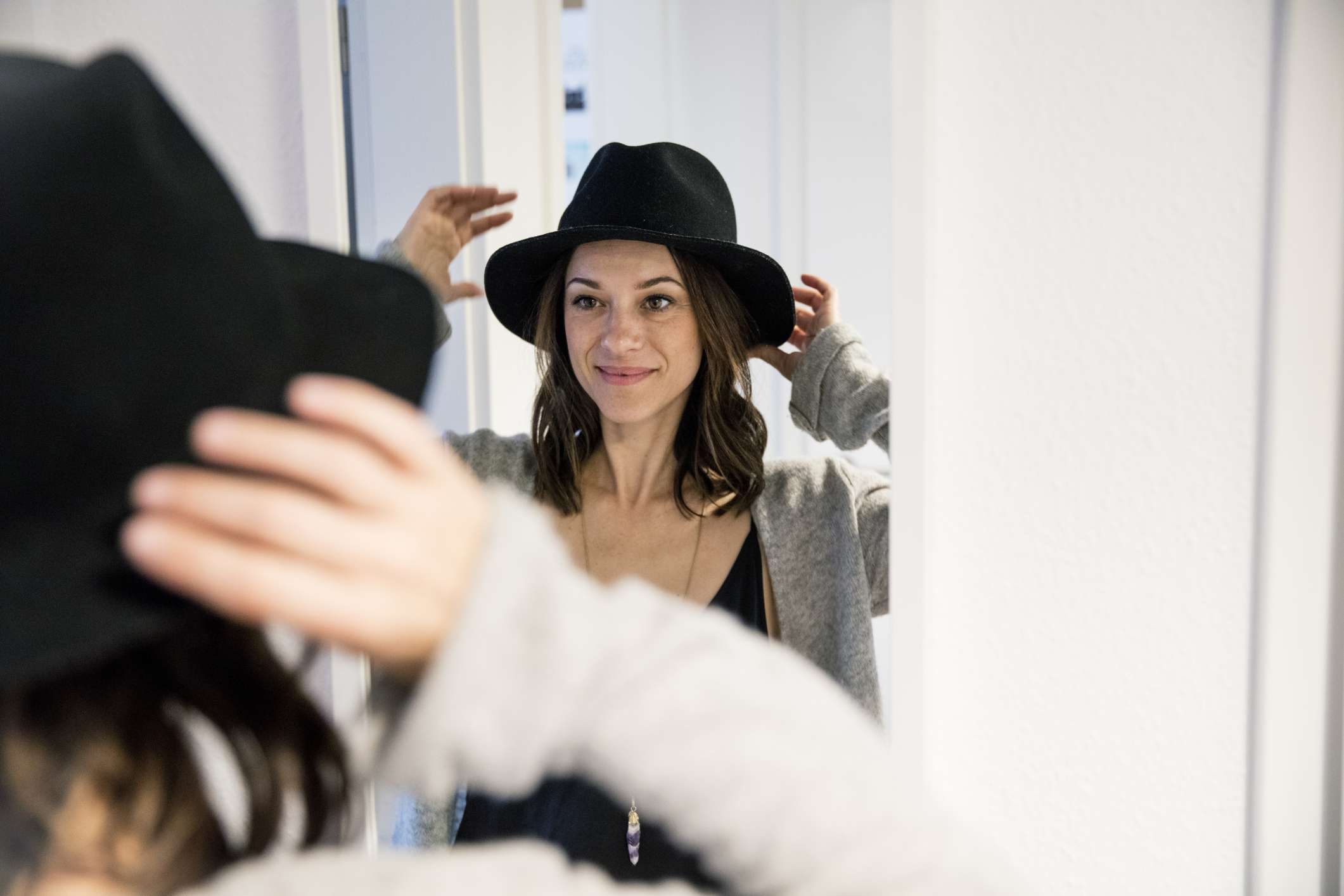 Woman tries on hat in mirror