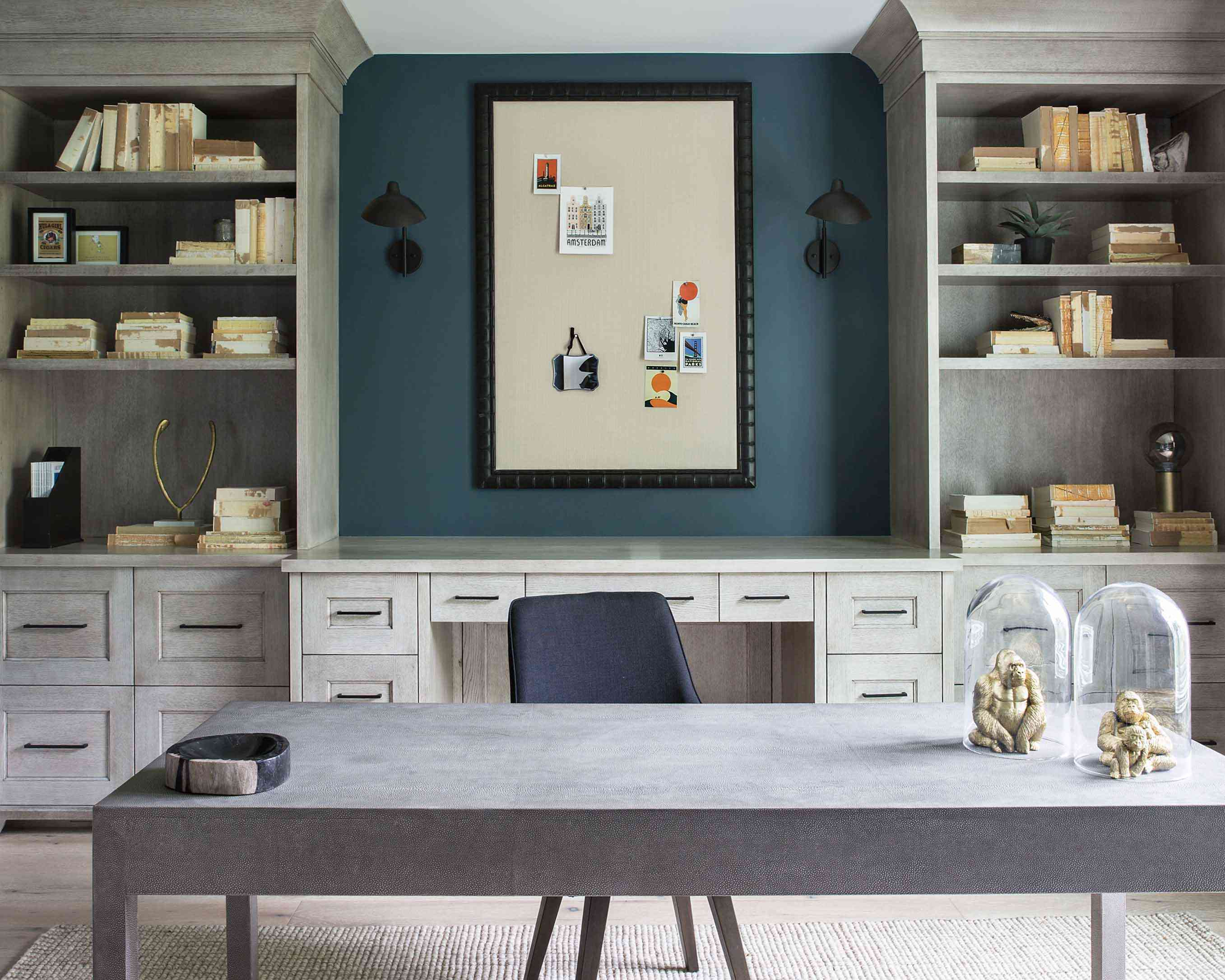 A home office decorated with gold gorilla sculptures and colorful snippets of paper