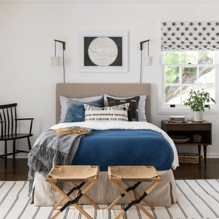 A bedroom with two dangling sconces that have been mounted over the headboard