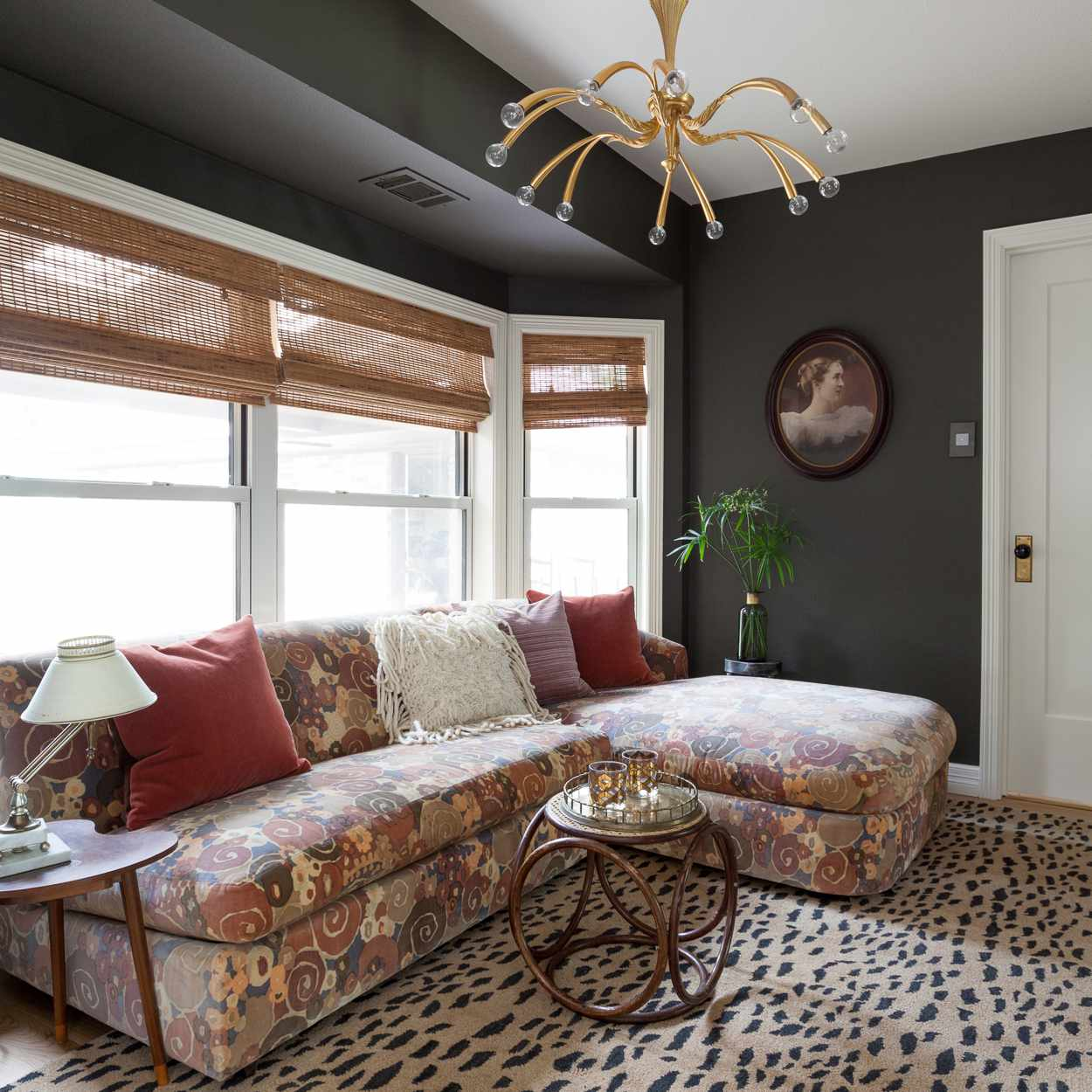 Eclectic living room features dark walls, couch and area rug in contrasting patterns