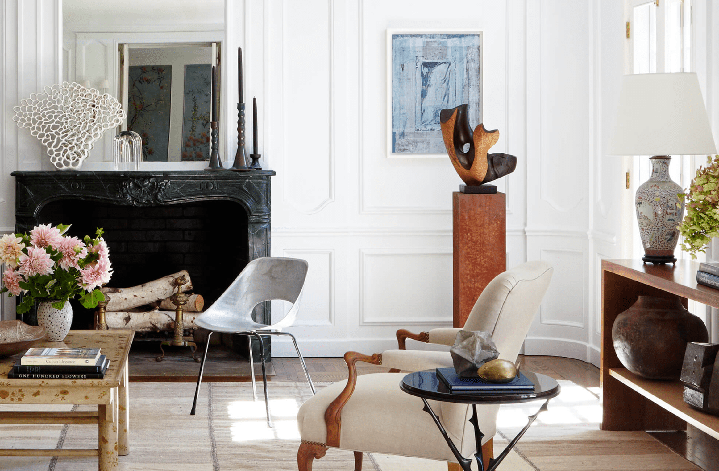 A living room filled with a mix of contemporary and antique furniture and decor
