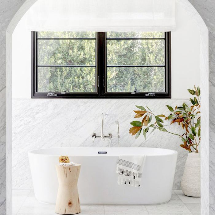 marble bathroom with arched entryway, black-trimmed windows