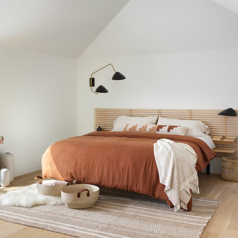 bedroom with woven rug and sunset-inspired bedding