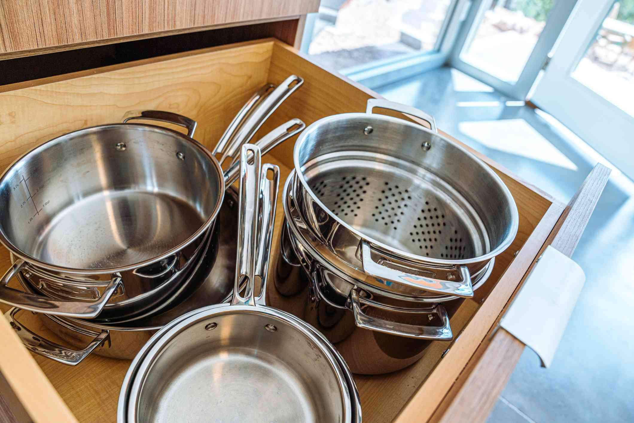 how to clean a burnt pot - clean pots organized in kitchen drawer