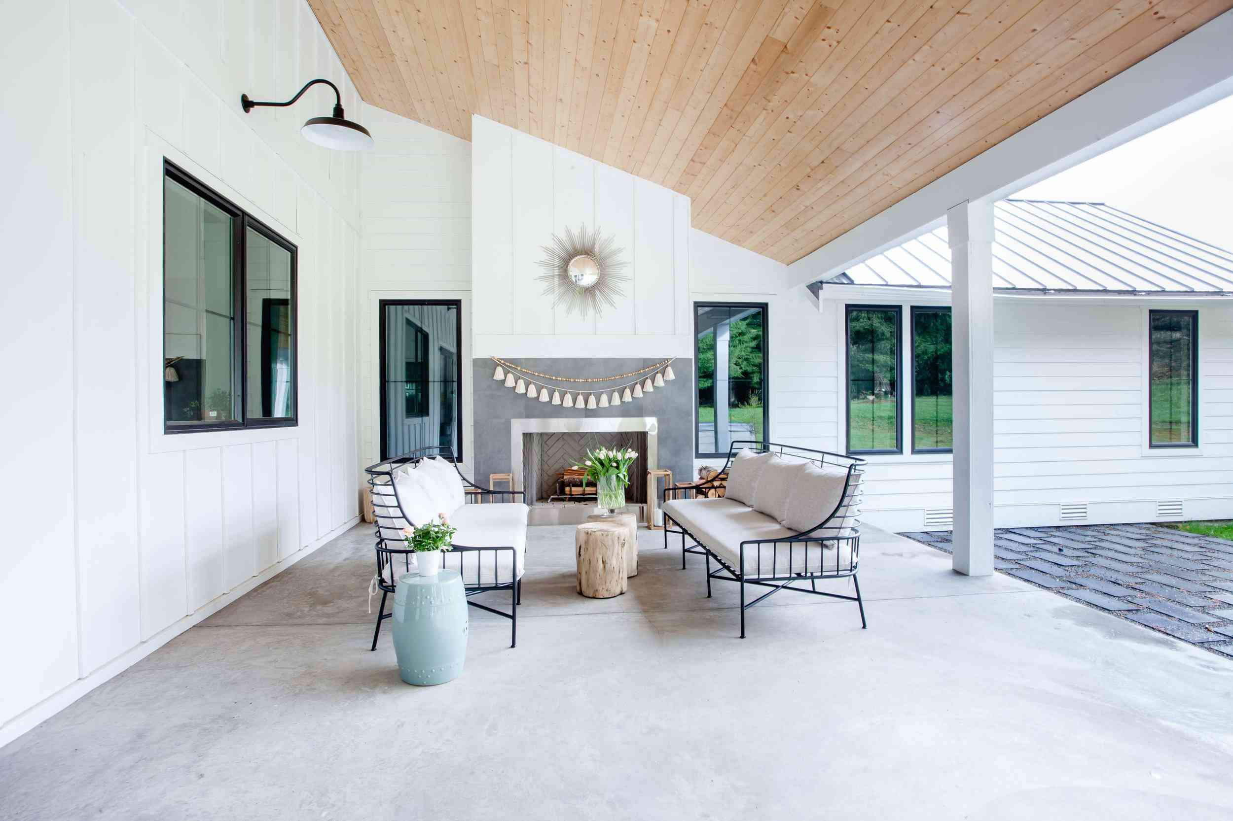 A covered patio with an outdoor fireplace that's been decorated with a fringe-lined garland