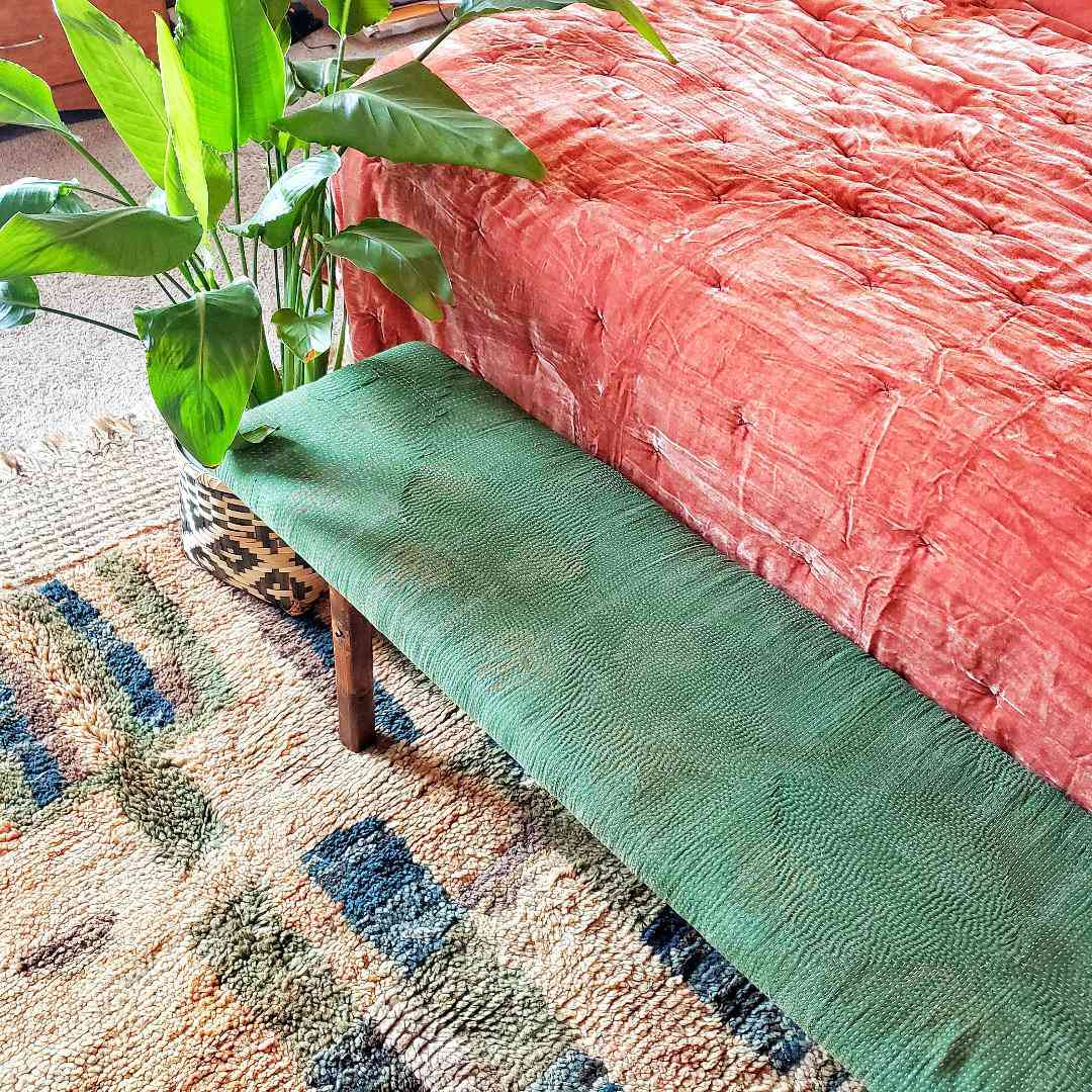 A bird of paradise sits next to a green upholstered bench at the foot of a bed.