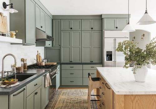 Brett Foken home tour - sage green kitchen with yellow rug and gray countertops