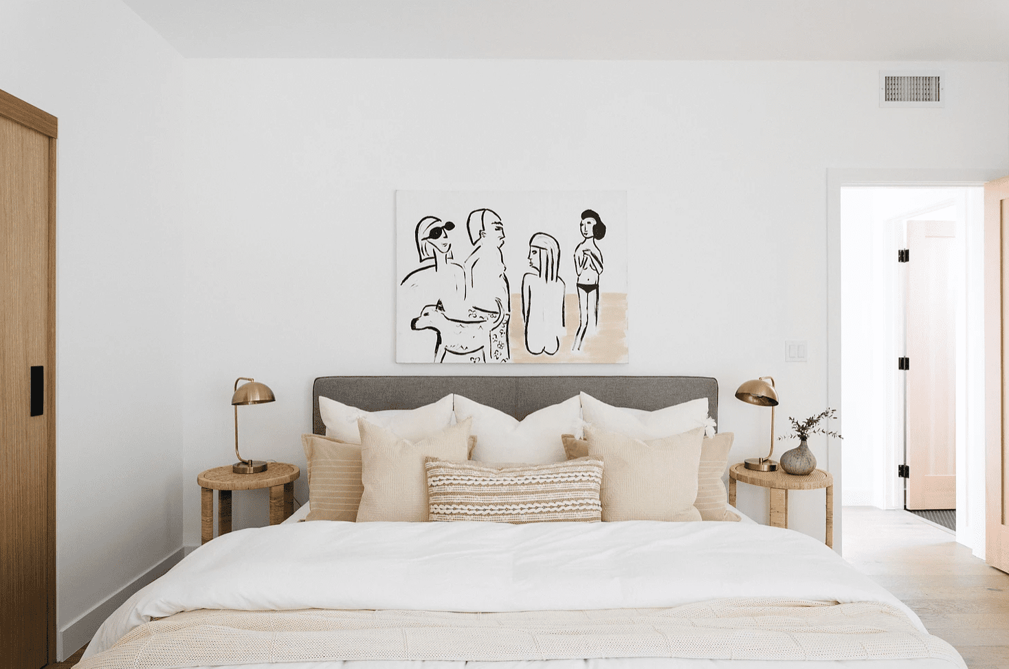 A bed with beige and white bedding and matching art