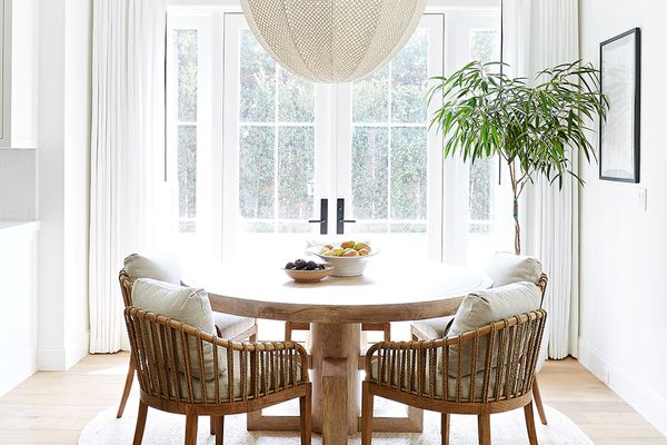 A dining room flanked by a set of glass doors, which have been framed with white curtains