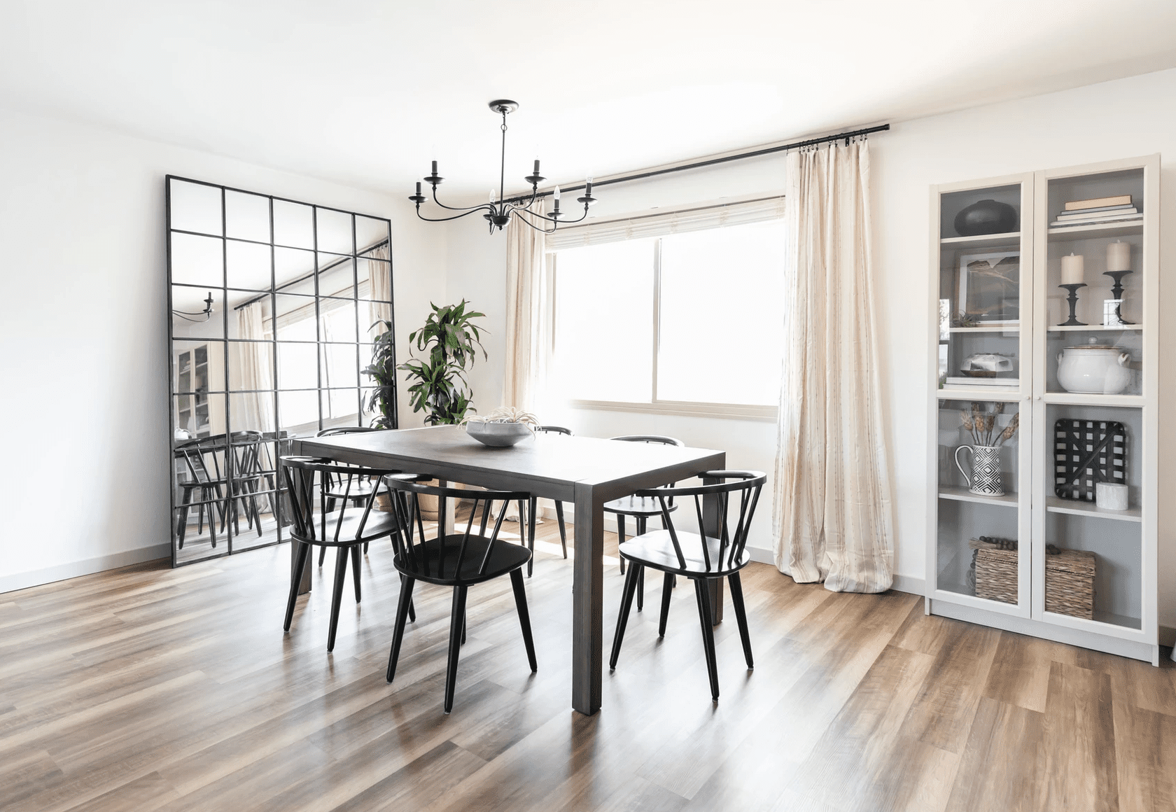 A dining room with a large floor mirror propped up against the wall