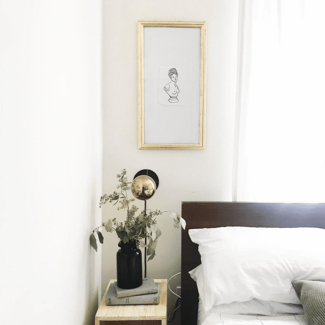 Framed small art above bed.
