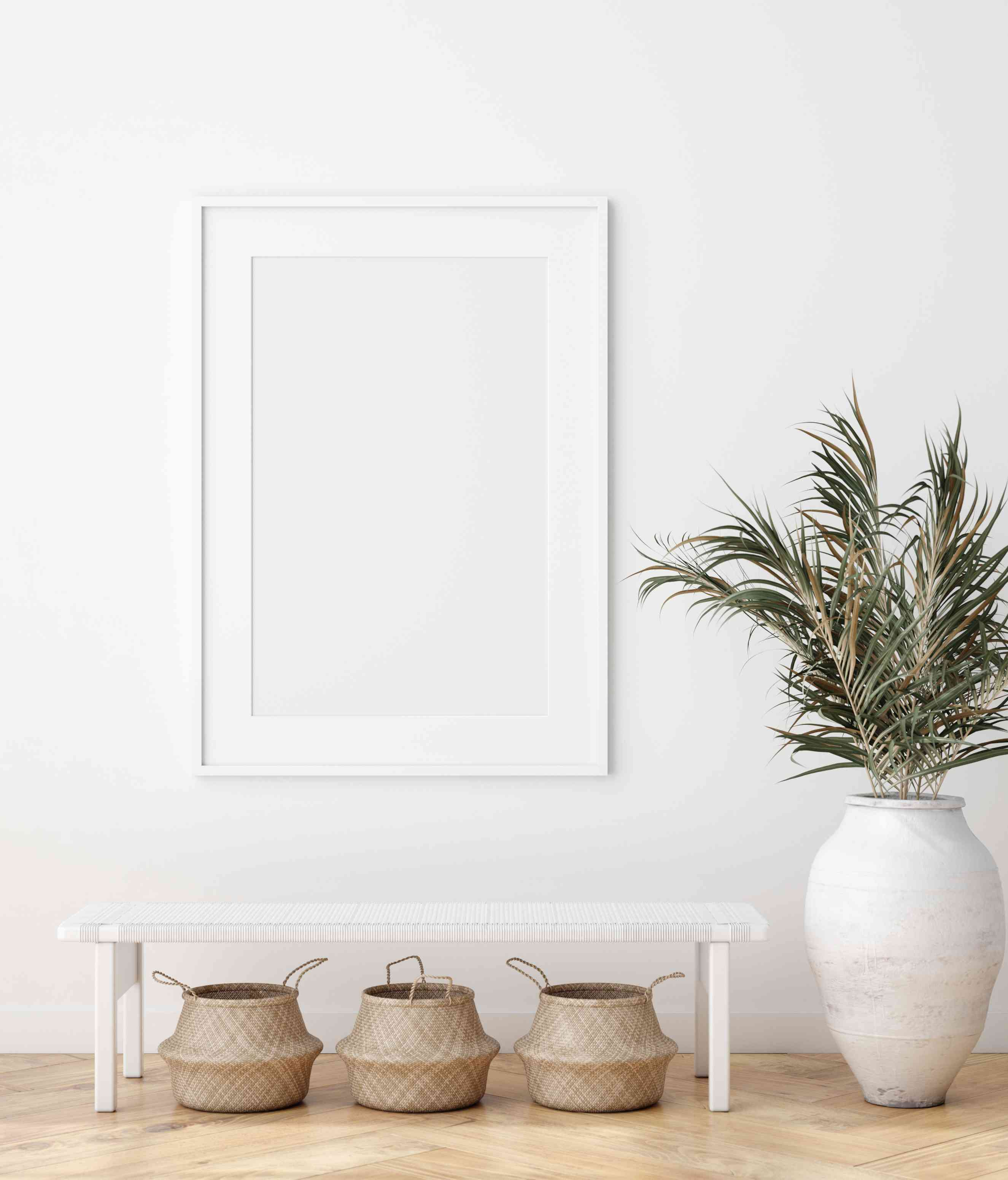 Minimalist interior with woven baskets beneath a white bench