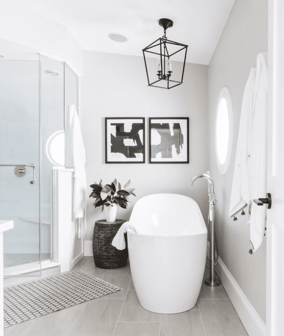 A small primary bathroom with a hexagonal shower and a bathtub that's been turned to face the shower