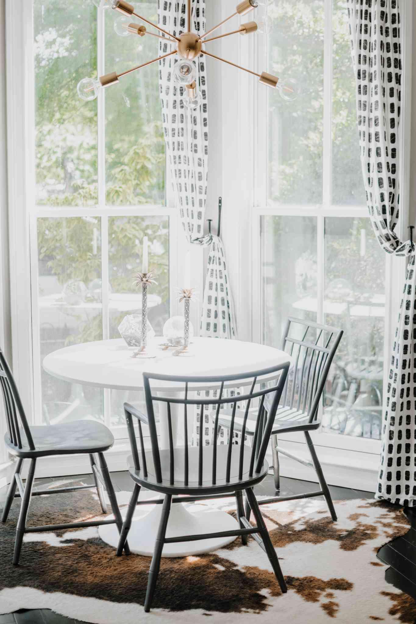 Styled midcentury dining room chairs under Sputnik chandelier.