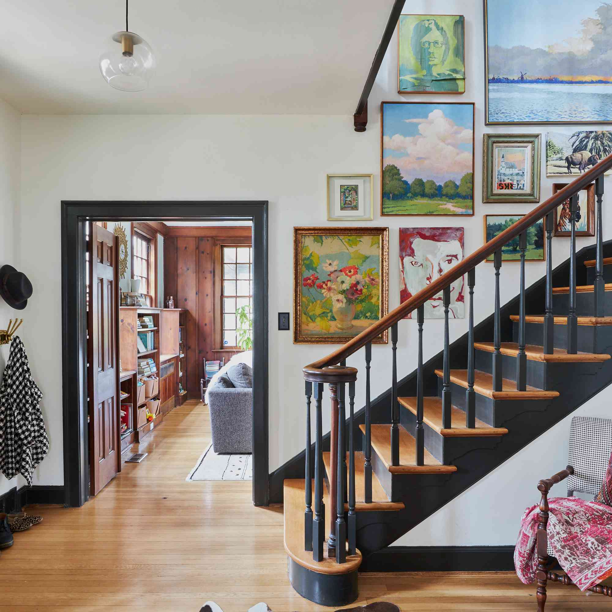 Eclectic gallery wall ascending staircase.