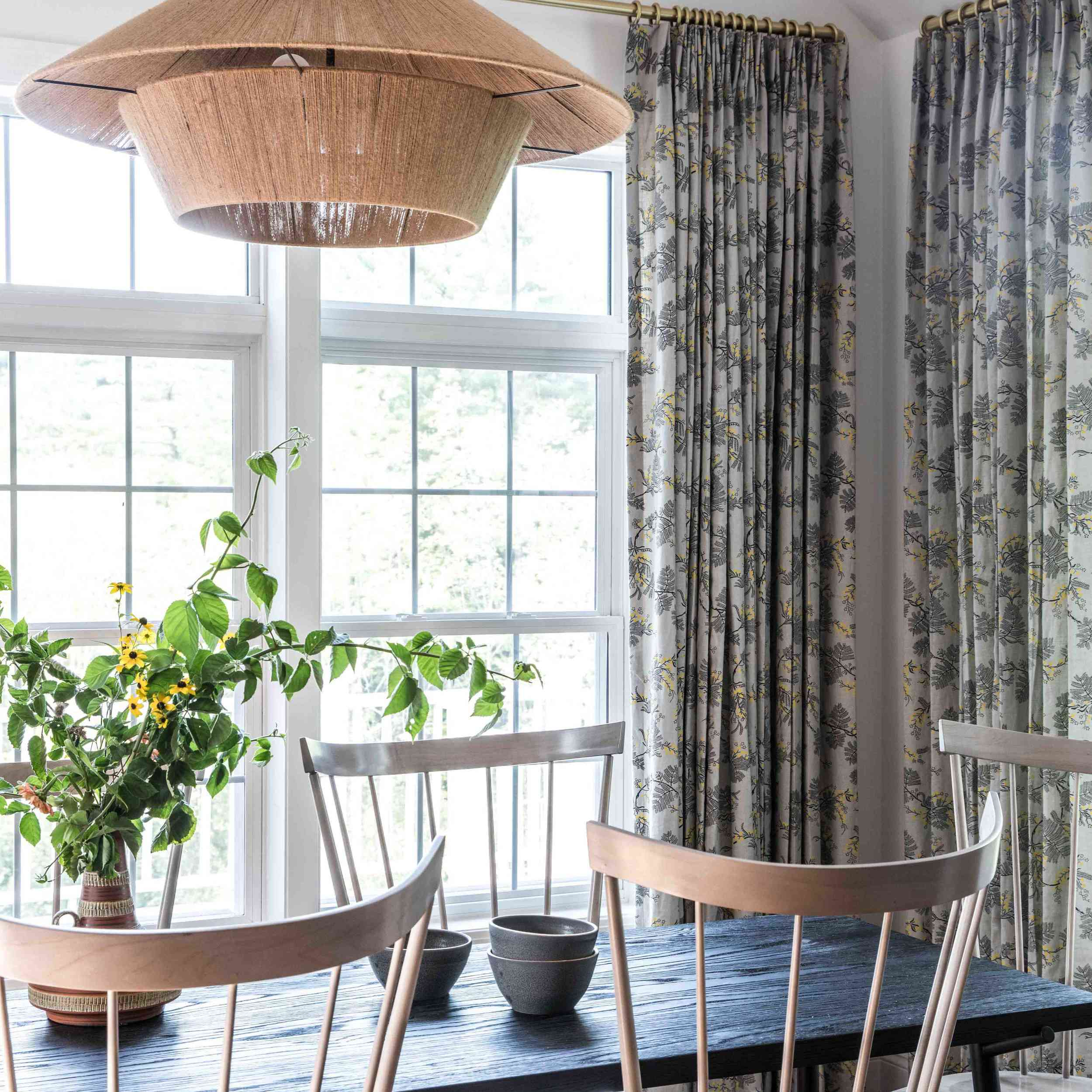 A neutral-filled dining room with printed light blue-gray curtains