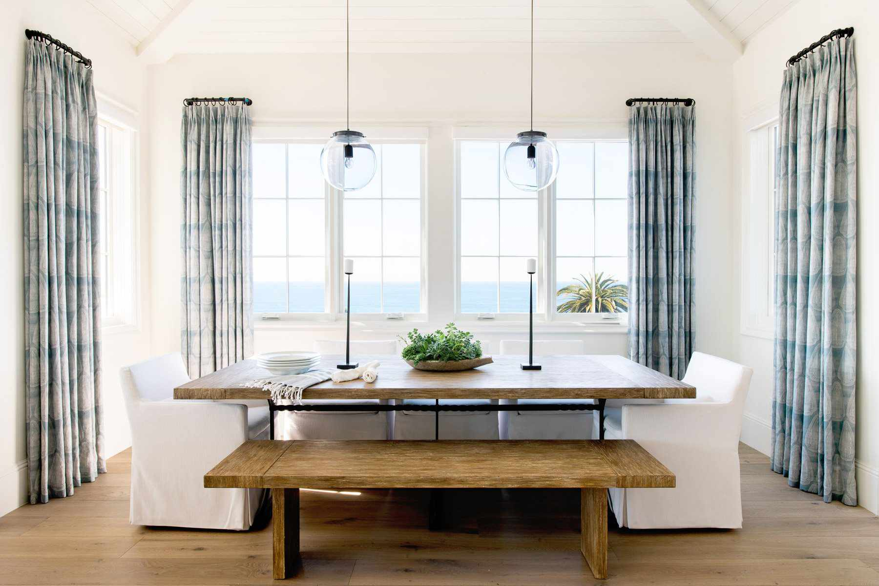A primarily white dining room lined with blue curtains