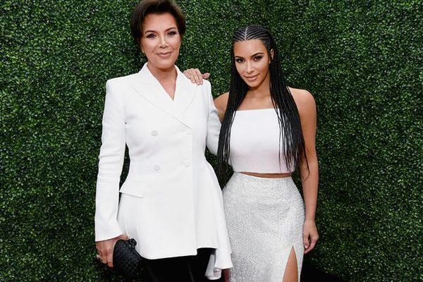 Kris Jenner with Kim Kardashian standing against a green leafy background.