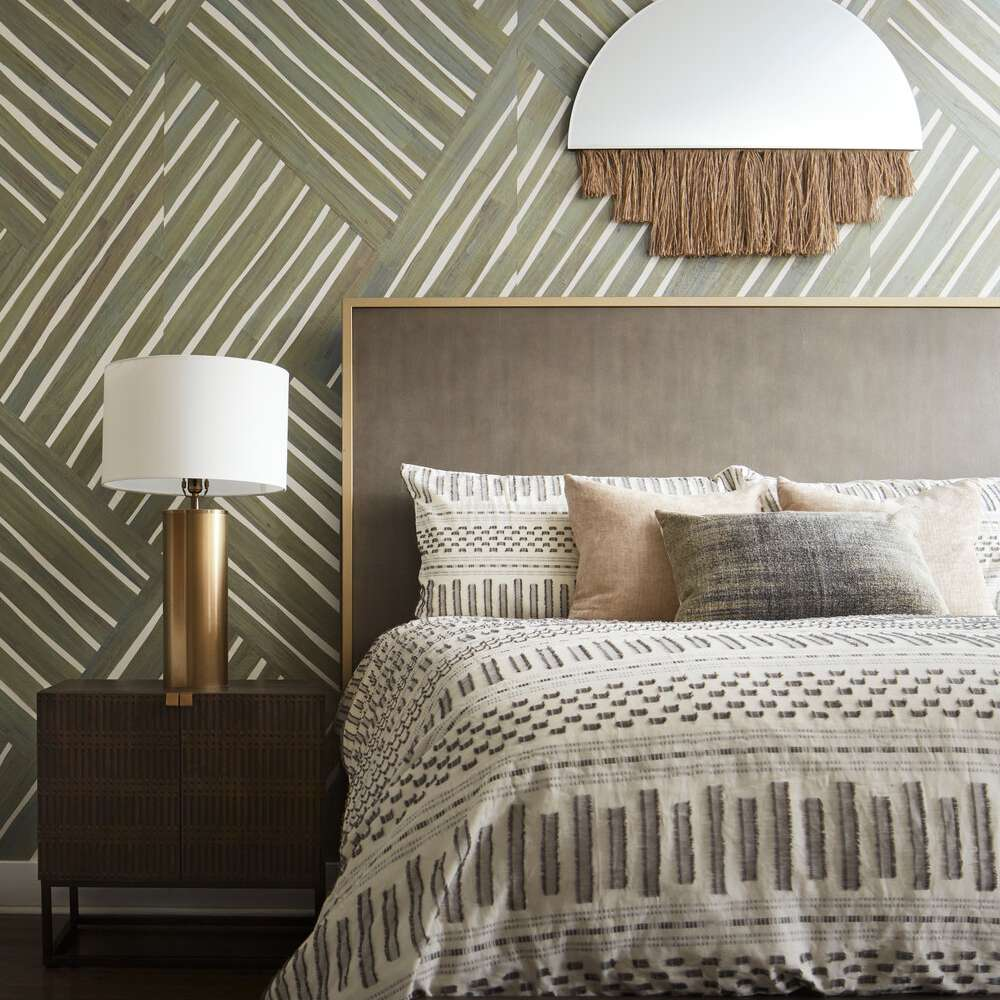 Bedroom with olive green patterned wallpaper and a fringed mirror