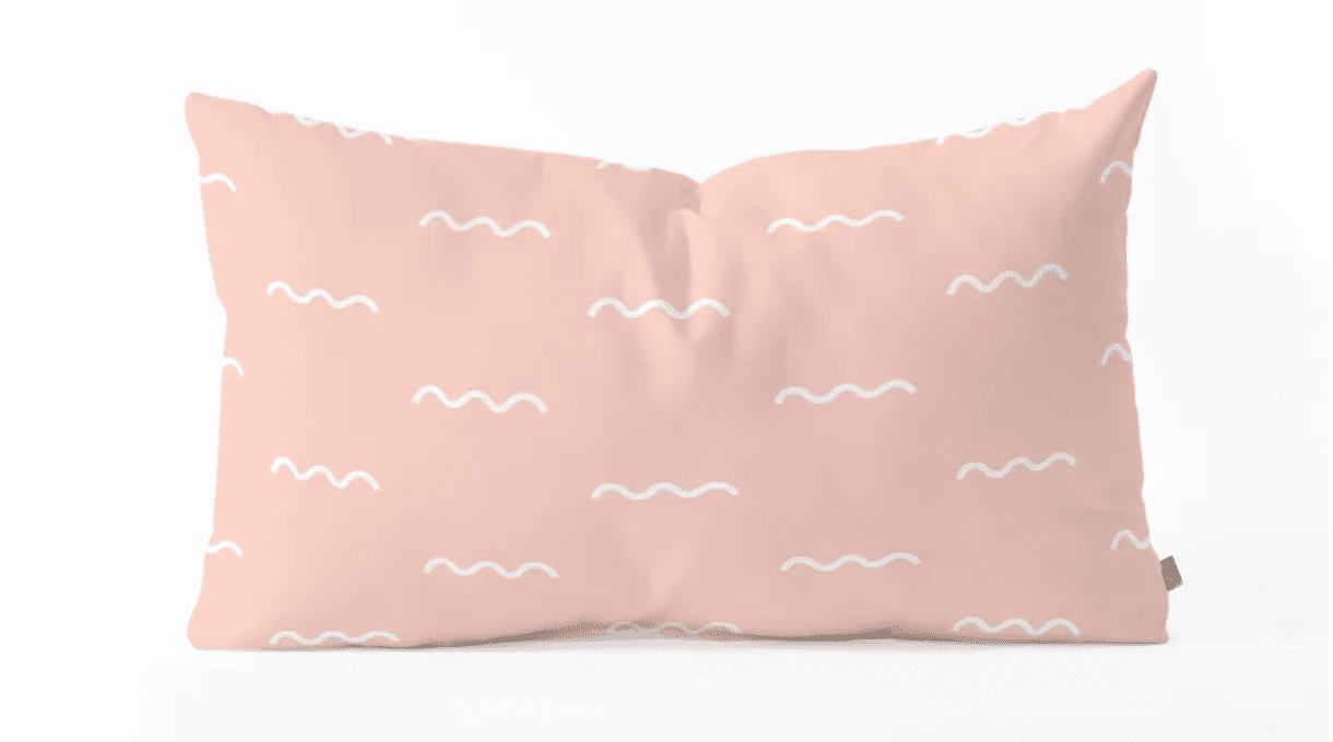 Pink lumbar pillow with white squiggles