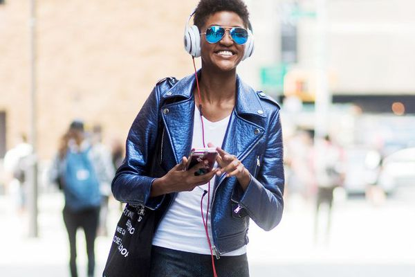 woman listening to headphones connected to phone