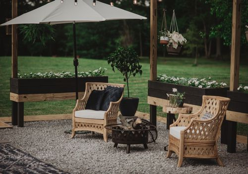 backyard with two armchairs and an umbrella surrounded by planters